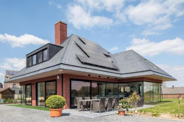 Moderne woning met rode gevelsteen en grote raampartijen (Haaltert)